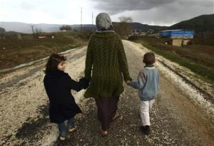Sawssan  Abdelwahab, who fled Idlib in Syria, walks with her children outside the refugees camp near the Turkish-Syrian border in Yayladagi